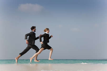 resolving: Business people running on beach LANG_EVOIMAGES