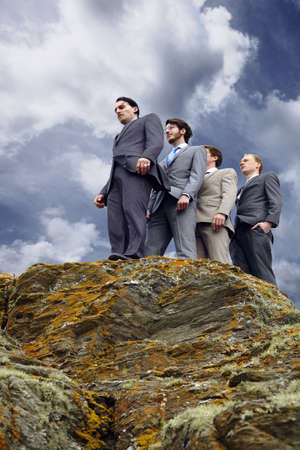 conforms: Businessmen standing on cliff edge