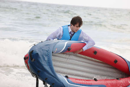survives: Businessman pulling canoe from ocean