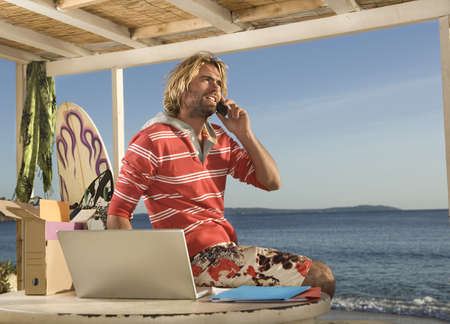surf man on phone and laptop at beach