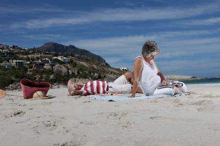 curare teneramente: Coppia più anziana rilassarsi insieme sulla spiaggia LANG_EVOIMAGES