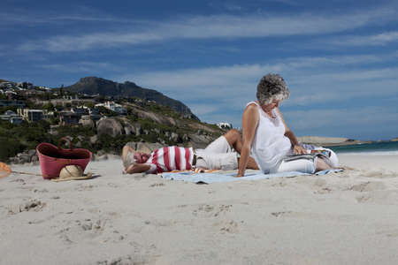 Older couple relaxing together on beach LANG_EVOIMAGES