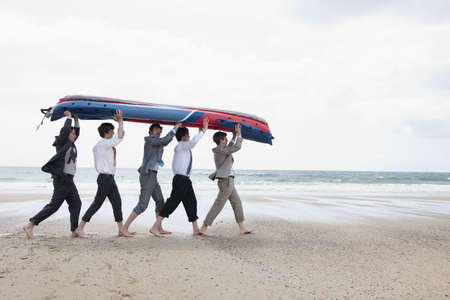 survives: Businessmen carrying canoe on beach