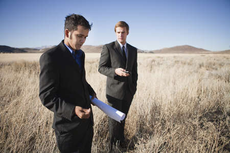affiliation: Two men with blueprints in field