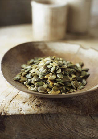 uncomplicated: Wooden bowl of pumpkin seeds LANG_EVOIMAGES
