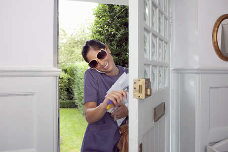 abodes: Woman on cell phone walking in door