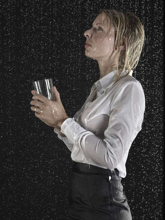 saturating: Businesswoman collecting rain in glass LANG_EVOIMAGES