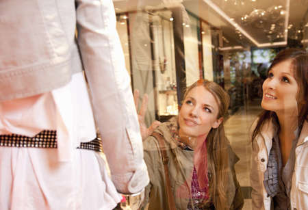 shopping buddies: Girls checking clothes in showcase