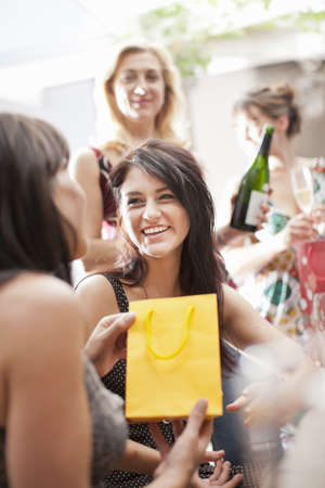 Smiling women exchanging gifts LANG_EVOIMAGES