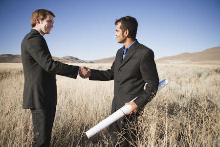 2 men with plans in field, shaking hands