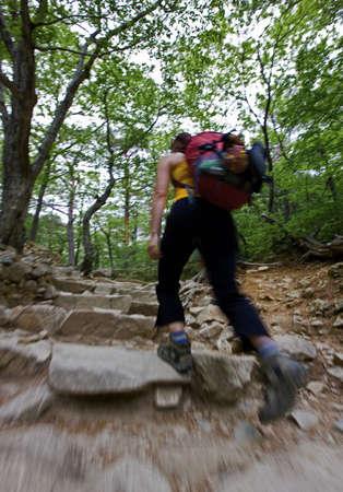 ascends: Woman hiking up rocky hillside