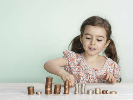 Girl stacking coins on counter LANG_EVOIMAGES