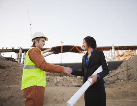 agrees: Man and woman on work site shaking hands