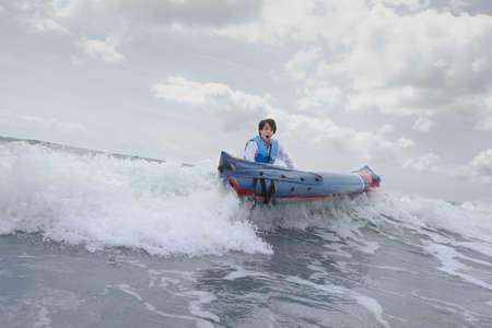 Businessman pushing canoe in ocean