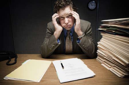 Stressed man at desk with paperwork LANG_EVOIMAGES