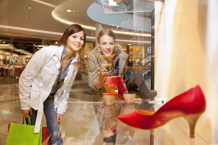 requiring: Girls checking out shoes in a showcase