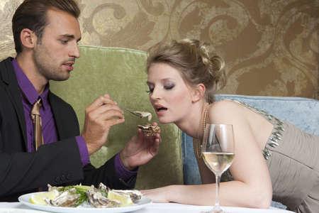 fed up: Man feeding girlfriend oysters