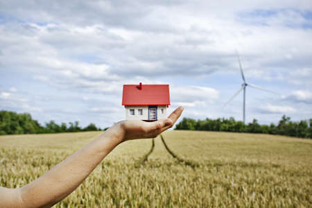 Woman with model house at wind turbines