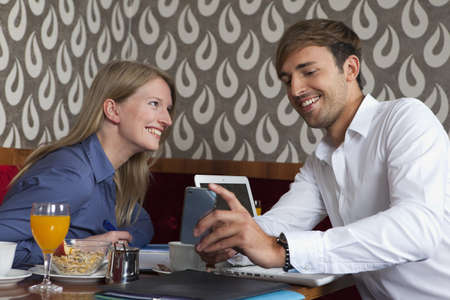 Smiling couple using cell phone in cafe LANG_EVOIMAGES