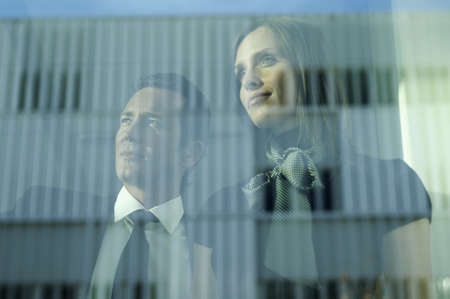 Businessman and woman looking out window