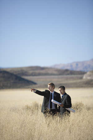 2 men with blueprints in field pointing LANG_EVOIMAGES