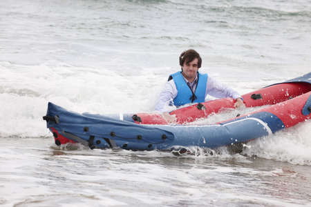 survives: Businessman pushing canoe in ocean