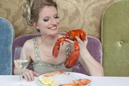 lavishly: Woman holding lobster in restaurant
