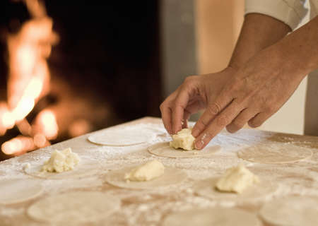 Cook filling pasta dough in kitchen LANG_EVOIMAGES