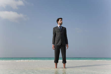 indecisive: Businessman standing on tropical beach