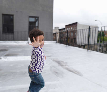 mischievious: Girl running on roof terrace, smiling