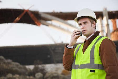 Man at worksite using walking talkie