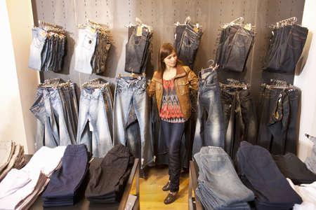 Girl choosing between two jeans LANG_EVOIMAGES