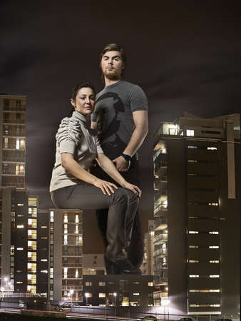 Oversized couple sitting on buildings LANG_EVOIMAGES