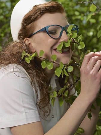 caregivers: Nurse in glasses smelling plants LANG_EVOIMAGES