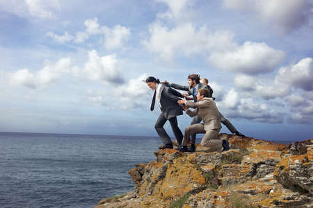 Businessmen pulling colleague from cliff LANG_EVOIMAGES