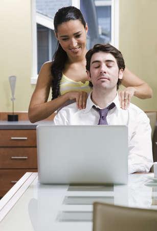 massage homme: femme aidant l'homme à se détendre à l'ordinateur LANG_EVOIMAGES