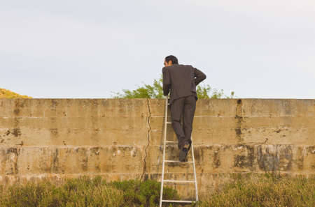 apalancamiento: Businessman climbing over the wall LANG_EVOIMAGES