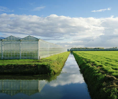 conservatories: Greenhouses and irrigated river in field
