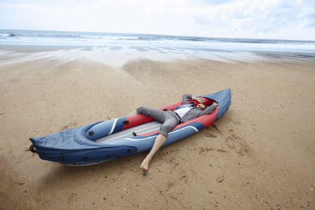 survives: Businessmen laying in canoe on beach