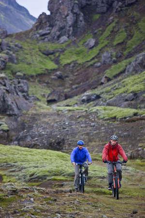 Men mountain biking on rocky path