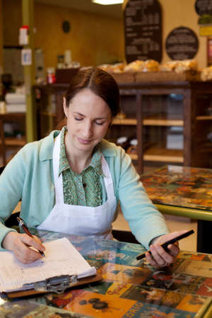 Woman working on accounts at bakery