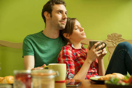 mornings: Young couple in kitchen relaxing over breakfast