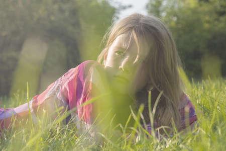 Girl sitting in grassy field LANG_EVOIMAGES