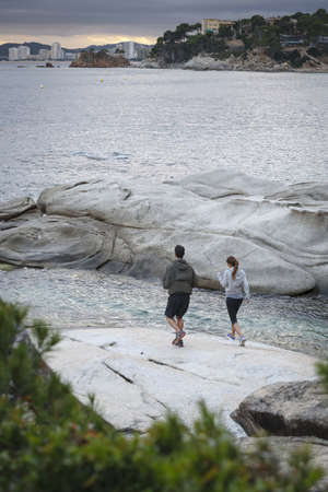 Couple walking on boulders by water LANG_EVOIMAGES