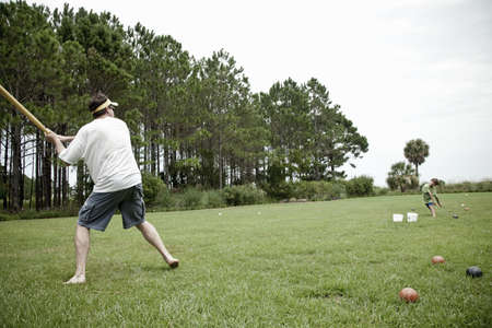 tosses: Father and son playing baseball in field