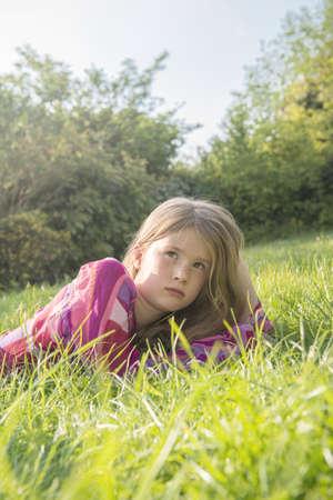 Girl laying in grassy field