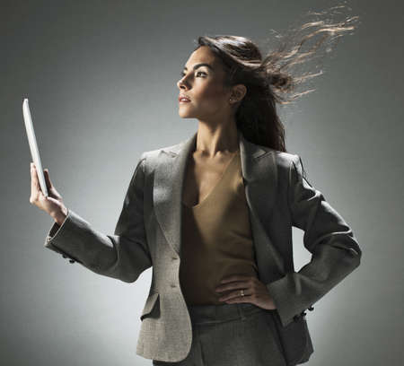 musing: Businesswoman holding tablet computer LANG_EVOIMAGES