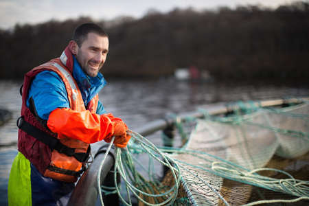 defended: Worker at salmon farm in rural lake LANG_EVOIMAGES