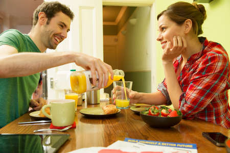 looking for love: Young couple at breakfast,man pouring orange juice LANG_EVOIMAGES