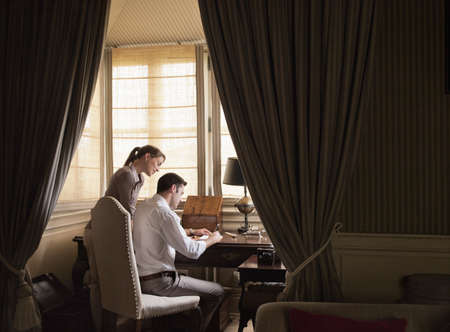 notations: Couple writing at desk in study LANG_EVOIMAGES